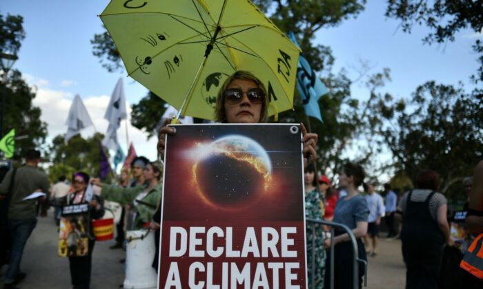 Demonstrators hold up placards outside the Australian Open venue during a climate protest rally in Melbourne, Australia on Jan. 24, 2020. (Photo by MANAN VATSYAYANA/AFP via Getty Images)