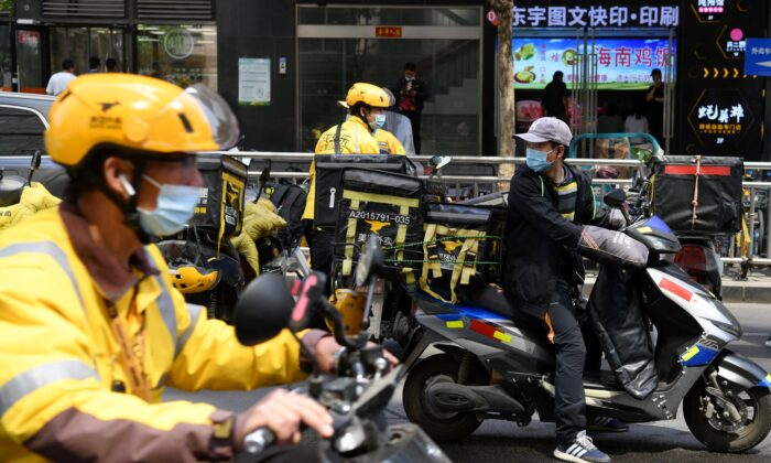 Delivery riders for Meituan, one of China's biggest food delivery firms, prepare to deliver lunch packages after picking them up from a restaurant in Beijing on April 27, 2021. (Greg Baker/AFP via Getty Images)