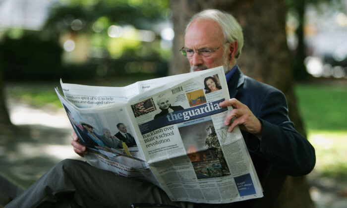 A man reads a copy of The Guardian newspaper in London, England, on Sept. 12, 2005. (Scott Barbour/Getty Images)
