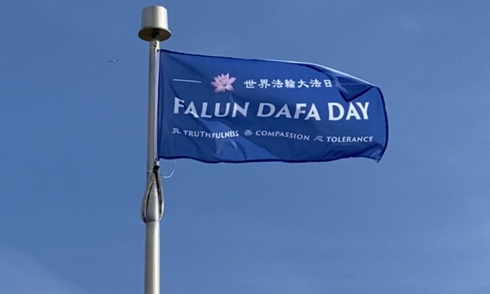 """A """"Falun Dafa Day"""" flag sways in the air after being raised by the Niagara Falls City Council ahead of World Falun Dafa Day in Niagara Falls, Canada, on May 8, 2021. (The Epoch Times)"""