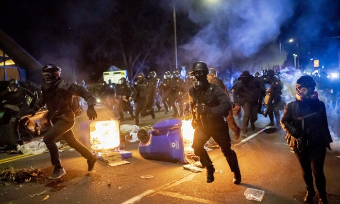 Portland police officers chase demonstrators after a riot was declared in Portland, Ore., on April 12, 2021. (Nathan Howard/Getty Images)