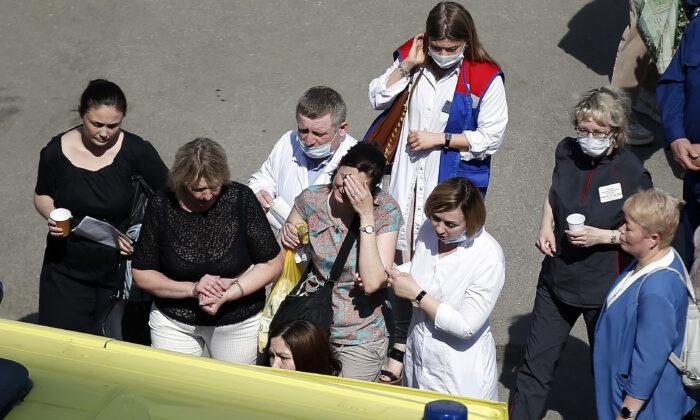 Medics and friends help a woman board an ambulance at a school after a shooting in Kazan, Russia, on May 11, 2021. (Roman Kruchinin/AP Photo)
