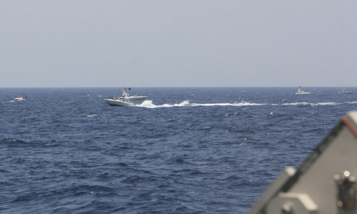 An Iranian Islamic Revolutionary Guard Corps Navy (IRGCN) fast in-shore attack craft (FIAC), a type of speedboat armed with machine guns, speeds near U.S. naval vessels transiting the Strait of Hormuz, on May 10, 2021. (U.S. Navy via AP)