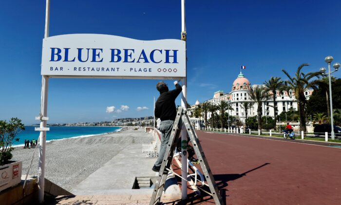 A man uses a ladder during preparations for the reopenning of restaurants and beaches in Nice as part of an easing of the country's lockdown restrictions amid the COVID-19 outbreak in France, on May 3, 2021.  (Eric Gaillard/Reuters)