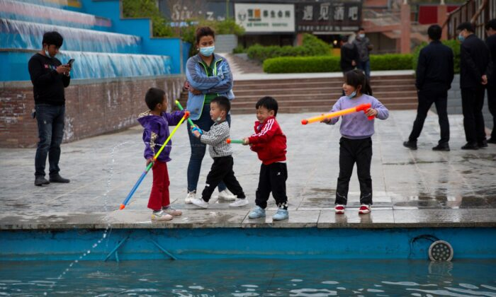 Children play with water toys at a public square in Aksu, Xinjiang Uyghur Autonomous Region, China, on April 20, 2021. (Mark Schiefelbein/AP Photo)