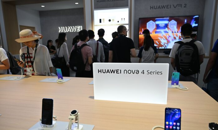 People look at the new Huawei smartphones at the company stand during the Consumer Electronics Show, Ces Asia 2019 in Shanghai on June 11, 2019. (HECTOR RETAMAL/AFP via Getty Images)
