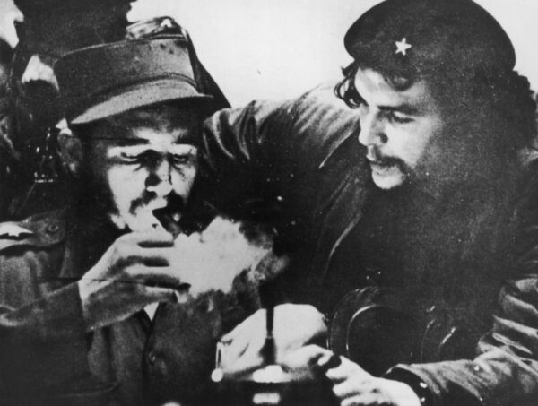 Cuban revolutionary Fidel Castro (left) lights his cigar while Argentine revolutionary Che Guevara (1928-1967) looks on in the early days of their guerrilla campaign in the Sierra Maestra Mountains of Cuba, circa 1956. Castro wears a military uniform while Guevara wears fatigues and a beret. (Hulton Archive/Getty Images)