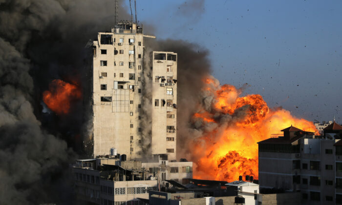 Smoke and flames rise from a tower building as it is destroyed by Israeli air strikes amid a flare-up of Israeli-Palestinian violence, in Gaza City on May 12, 2021. (Ibraheem Abu Mustafa/Reuters)