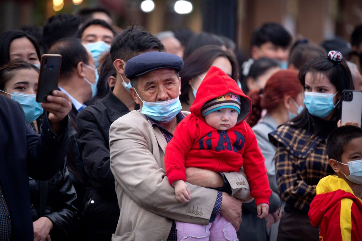 man holds a child in Xinjiang