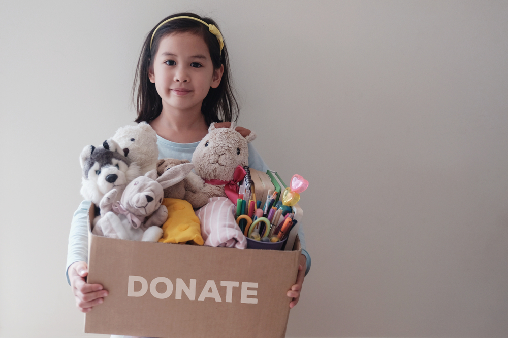 Mixed,Asian,Young,Volunteer,Girl,Holding,A,Box,Full,Of