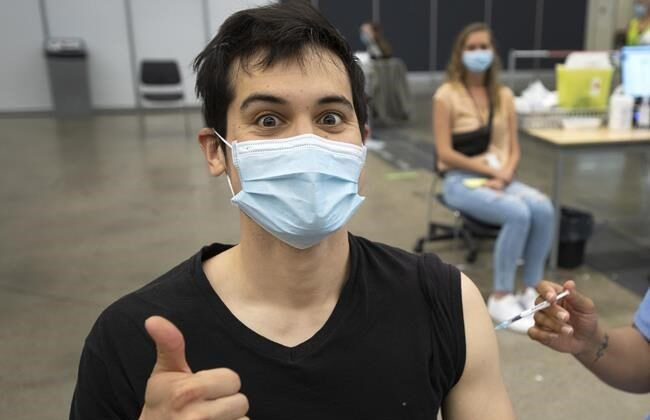 Adam Feller reacts as he gets his Pfizer-BioNTech shot at a COVID-19 vaccination clinic on May 13, 2021, in Montreal. Quebec has become the latest province to stop giving Oxford-AstraZeneca COVID-19 shot as a first dose. (Ryan Remiorz/The Canadian Press)
