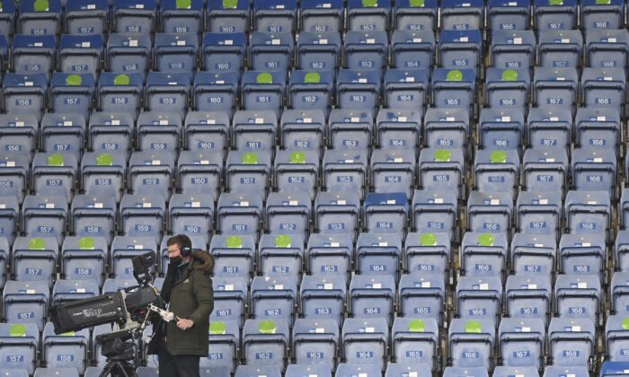A TV cameraman sets up his camera before the start of the English Premier League soccer match between Chelsea and Fulham at Stamford Bridge Stadium in London, on May 1, 2021. (Justin Setterfield/Pool via AP)