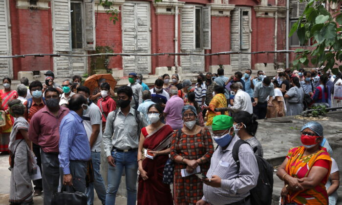 People wearing protective face masks wait to receive their second dose of COVISHIELD, a COVID-19 vaccine manufactured by Serum Institute of India, outside a vaccination centre in Kolkata, India, May 12, 2021. (Rupak De Chowdhuri/Reuters)