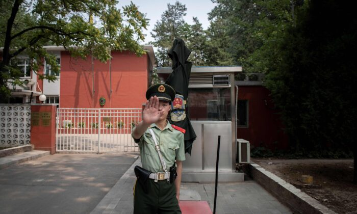 A paramilitary police officer gestures outside the Belgium embassy in Beijing on June 19, 2019. - A Belgian diplomat was expected to travel to China's restive Xinjiang region on June 18 to confirm the whereabouts of a Uyghur family that was escorted from Belgium's embassy in Beijing by police last month. (NICOLAS ASFOURI /AFP via Getty Images)