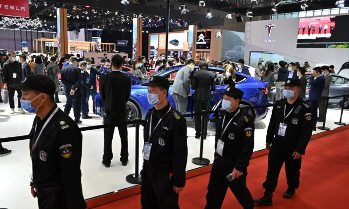 Guards walk near a Tesla stand during the 19th Shanghai International Automobile Industry Exhibition in Shanghai on April 19, 2021. (Photo by Hector RETAMAL / AFP) (Photo by HECTOR RETAMAL/AFP via Getty Images)