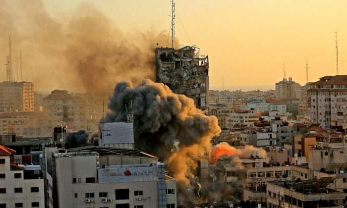 Heavy smoke and fire rise from Al-Sharouk tower as it collapses after being hit by an Israeli air strike, in Gaza City, on May 12, 2021. (Qusay Dawud/AFP via Getty Images)