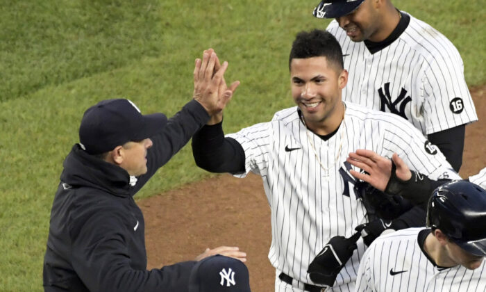New York Yankees' Gleyber Torres is congratulated by manager Aaron Boone after Torres drove in the winning run in the 11th inning of the team's baseball game against the Washington Nationals at Yankee Stadium in New York City on May 8, 2021. (Bill Kostroun/AP Photo)