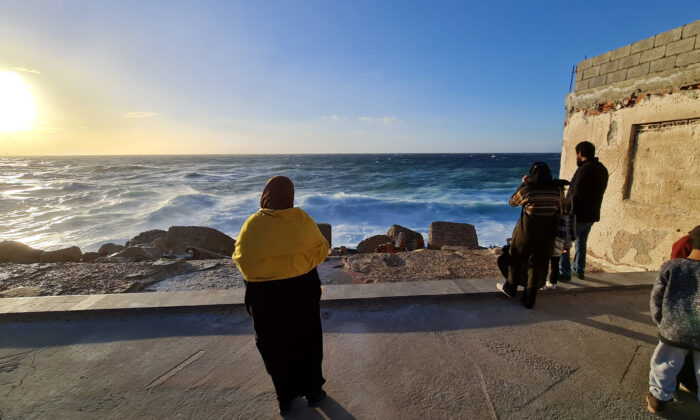 Libyans stand on the shore of the Mediterranean Sea in the capital Tripoli, Libya, on Jan. 26, 2021. (Mahmud Turkia/AFP via Getty Images)