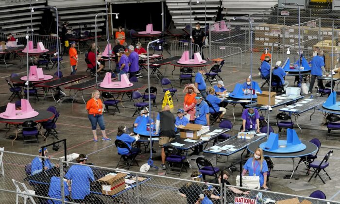 Maricopa County ballots cast in the 2020 general election are examined and recounted by contractors working for Florida-based company, Cyber Ninjas, at Veterans Memorial Coliseum in Phoenix, Ariz., on May 6, 2021. (Matt York/AP Photo/Pool)