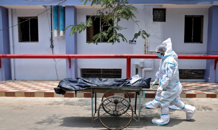 Healthcare workers transfer the body of a person who died from COVID-19, in Kolkata, India, on May 12, 2021. (Rupak De Chowdhuri/Reuters)