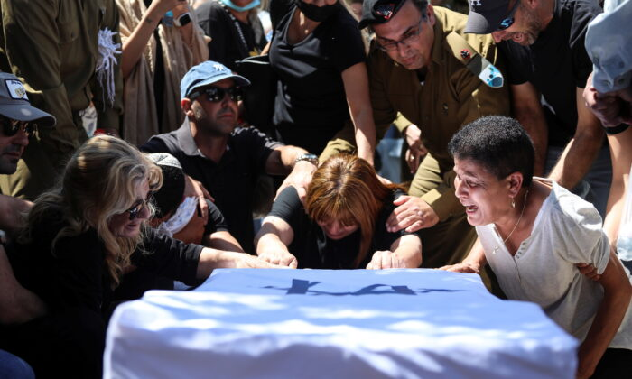 Family and friends, including Israeli soldiers, mourn over the flag-covered coffin of Israeli soldier Omer Tabib, who was killed during cross-border fighting with Gaza, at his funeral in Eliakim, Israel, on May 13, 2021. (Avishag Shar-Yashuv/Reuters)