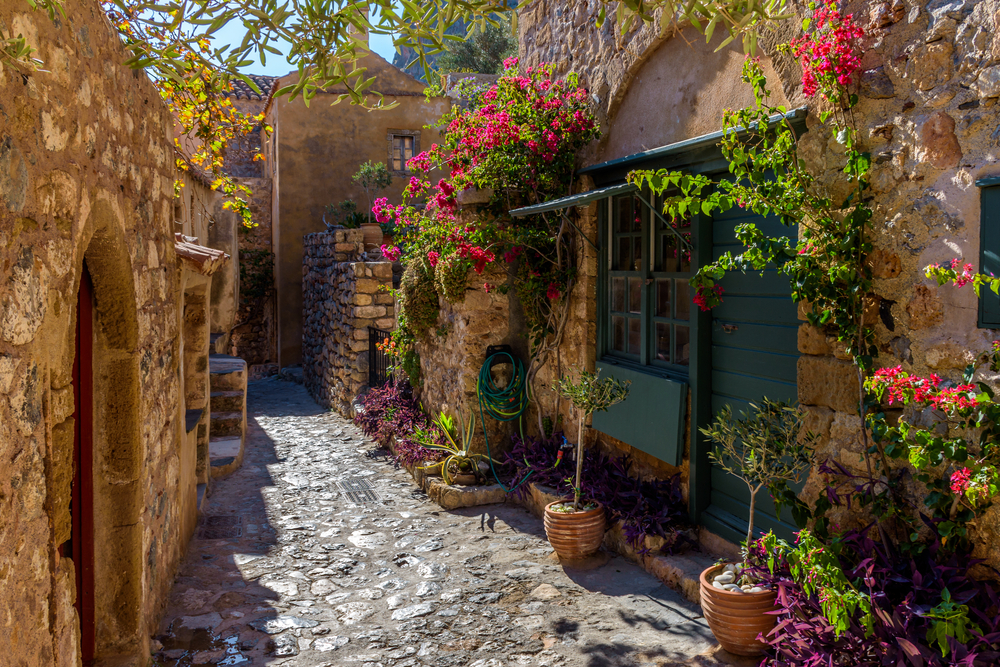 Traditional,Architecture,With,Narrow,Stone,Street,And,A,Colorfull,Bougainvillea