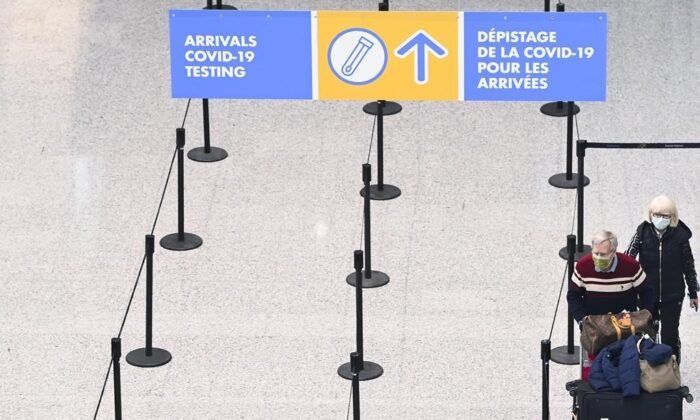 Travellers are directed to take a mandatory COVID-19 test after arriving on a international flight at Pearson International Airport in Toronto, on Feb. 1, 2021. The number of planes landing in Canada carrying at least one passenger who has COVID-19 was cut by more than half in the two weeks after the federal government barred incoming flights from India and Pakistan.   (Nathan Denette / The Canadian Press)