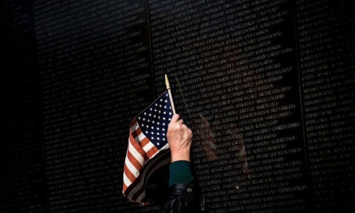 A man points to a name while visiting the Vietnam War Memorial on Veterans Day in Washington, D.C. on Nov. 10, 2017. (Brendan Smialowski/AFP via Getty Images)