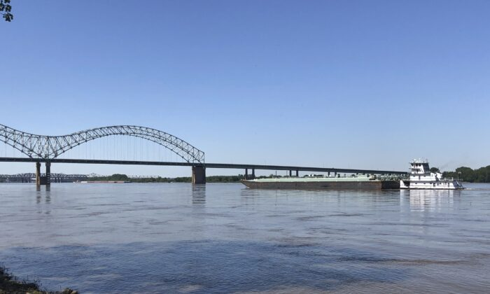A boat hauling barges down the Mississippi River moves toward the Interstate 40 bridge linking Tennessee and Arkansas in Memphis, Tenn., on May 14, 2021. (Adrian Sainz/AP Photo)