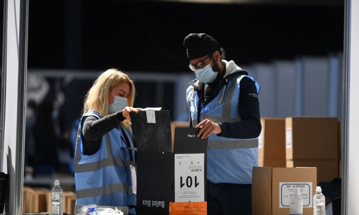 Staff open a ballot box to count for the local elections at the count centre at Olympia London in west London on May 7, 2021. (Justin Tallis/AFP via Getty Images)