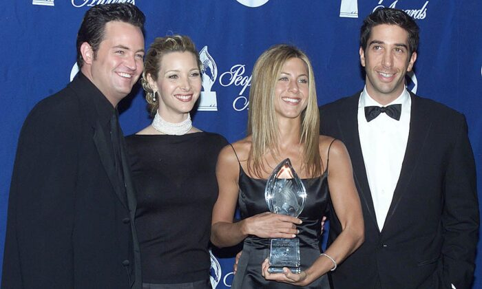 """The cast of the television comedy """"Friends"""" (From L-R:) Matthew Perry, Lisa Kudrow, Jennifer Aniston, and David Schwimmer pose with their award at the 26th People's Choice Awards in Pasadena, Calif., on Jan. 9, 2000. (Lucy Nicholson/AFP via Getty Images)"""