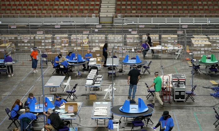 Maricopa County ballots cast in the 2020 general election are examined and recounted by contractors working for Florida-based company, Cyber Ninjas, at Veterans Memorial Coliseum in Phoenix, Ariz., on May 6, 2021. (Matt York/Pool/AP Photo)