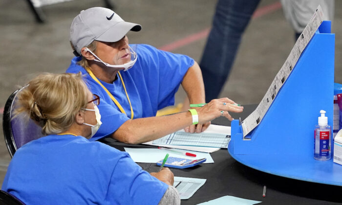 Ballots cast in the 2020 general election are examined and recounted by contractors working for Florida-based company, Cyber Ninjas, at Veterans Memorial Coliseum in Phoenix, Ariz., on May 6, 2021. (Matt York/Pool/AP Photo)