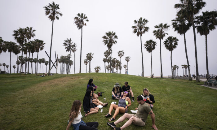 A group of friends, who said they are fully vaccinated for COVID-19, mingle on the beach in Los Angeles, Calif., on May 5, 2021. (Jae C. Hong/AP Photo)