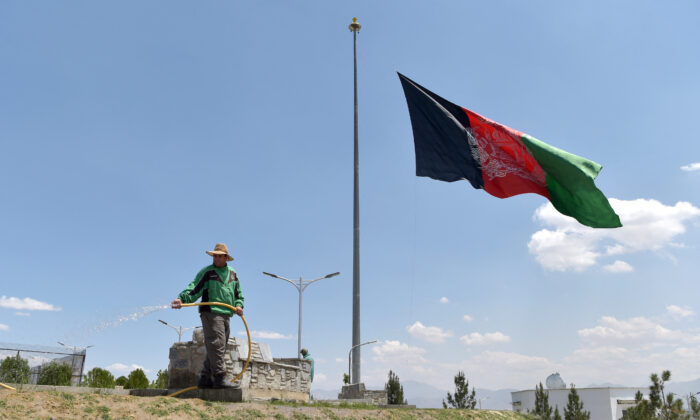 A worker waters a lawn near an Afghan national flag flying at half-mast in Kabul on May 11, 2021. May 11 was declared a national day of mourning by Afghan President Ashraf Ghani to condemn the recent terrorist attacks. (WAKIL KOHSAR/AFP via Getty Images)