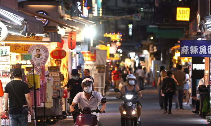People wear protective masks as they ride their motorbikes as others shop at a night market in Taipei, Taiwan, on May 15, 2021. (Ann Wang/Reuters)