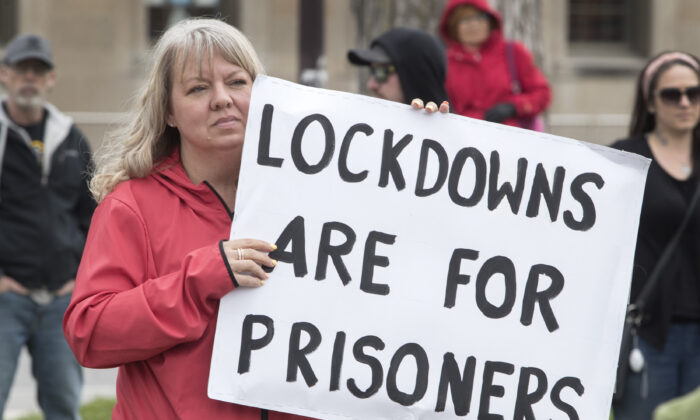 In a file photo, demonstrators march at a protest against COVID-19 restrictions, in Peterborough, Ont., on April 24, 2021. Several anti-lockdown protests were held in different cities in Canada on May 15. (The Canadian Press/Fred Thornhill)