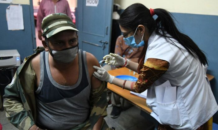 A medical worker inoculates a Border Security Force (BSF) personnel with a dose of the Covishield, ChAdOx1 nCoV-19 coronavirus vaccine, at a civil hospital in Ajnala village, about 28 km from Amritsaron April 1, 2021, as India expanded its coronavirus vaccination drive to the 45-60 age group. (Narinder Nanu/AFP)