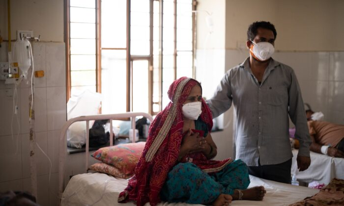 An Indian relative comforts a patient as she receives supplemental oxygen during treatment for the coronavirus at the Kapil Government Hospital, which became a coronavirus consultation and treatment facility serving villages in the Jaipur and Sikar districts, in Neem Ka Thana, Sikar District, Rajasthan, India, on May 15, 2021 (Rebecca Conway/Getty Images)