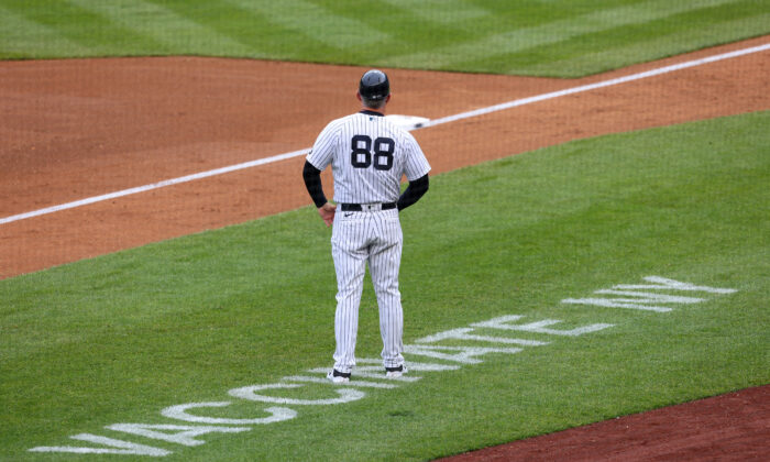 Third base coach Phil Nevin #88 of the New York Yankees stands near the coaching box as Vaccinate NY is painted on the field during a game against the Washington Nationals at Yankee Stadium in New York City on May 8, 2021. Nevin was among members of the New York Yankees who have tested positive for COVID-19. (Rich Schultz/Getty Images)