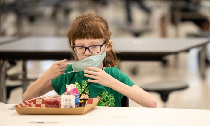 A child puts her mask back on after finishing lunch at a socially distanced table in the cafeteria of Medora Elementary School in Louisville, Ky., on March 17, 2021. (Jon Cherry/Getty Images)