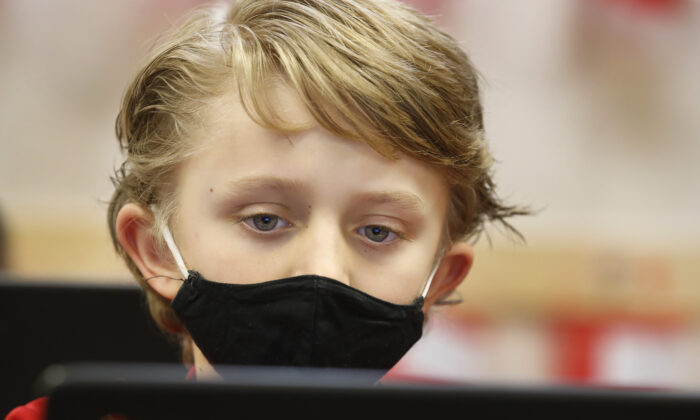 A student wears a mask as he does his work at Freedom Preparatory Academy in Provo, Utah, on Feb. 10, 2021. (George Frey/Getty Images)