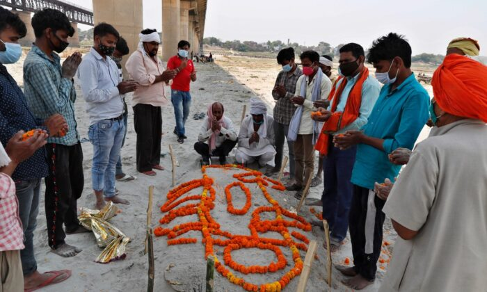 Family members and relatives of a person who died pray next to his shallow sand grave on the banks of river Ganges in Prayagraj, India, on May 16, 2021. (Rajesh Kumar Singh/AP Photo)
