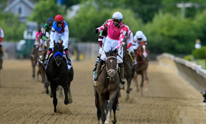 Flavien Prat atop Rombauer (C) reacts after winning the Preakness Stakes horse race at Pimlico Race Course,  in Baltimore, on May 15, 2021. (Nick Wass/AP Photo)