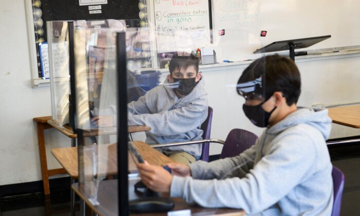 Students sit behind barriers and use tablets during an in-person English class at St. Anthony Catholic High School during the COVID-19 pandemic in Long Beach, Calif., on March 24, 2021. (Patrick T. Fallon/AFP via Getty Images)