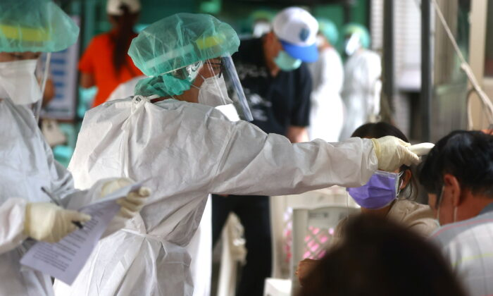 A healthcare frontline worker prepares people to get their rapid test following a surge of coronavirus disease (COVID-19) infections in Taipei, Taiwan, on May 17, 2021. (Ann Wang/Reuters)