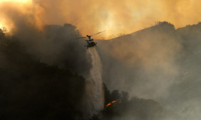 A firefighting helicopter drops water onto a brush fire scorching at least 100 acres in the Pacific Palisades area of Los Angeles, Calif., on May 15, 2021. (Ringo H.W. Chiu/AP Photo)