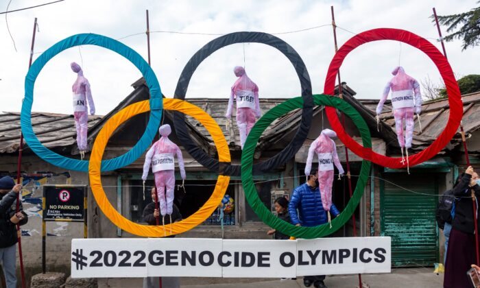 Exile Tibetans use the Olympic Rings as a prop as they hold a street protest against the holding of the 2022 Beijing Winter Olympics, in Dharmsala, India, on Feb. 3, 2021. (Ashwini Bhatia/AP Photo)