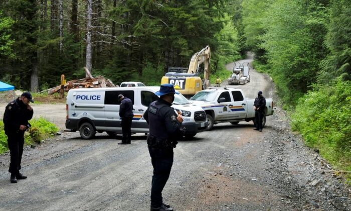An excavator works in the background as police establish a checkpoint on McClure Main in the Caycuse area on B.C.'s Vancouver Island, on May 17, 2021. (Jen Osborne/The Canadian Press)