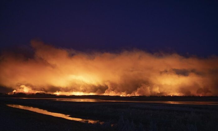 A forest fire burns late into the evening northeast of Prince Albert, Sask., on May 17, 2021. ( Kayle Neis / The Canadian Press)